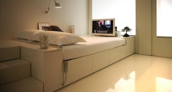 Ložnice je celá v bílém. Pohyblivá stěna je odsunutá na maximum. V nohách postele je výsuvná LCD televize