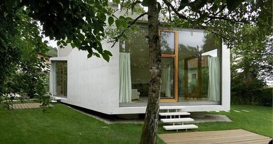 Struktura z leštěného bílého betonu vypadá jako skála náhodně vhozená do zahrady.
