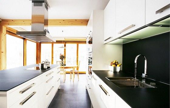 Dvě stěny kuchyně má Ester Janečková prosklené, pracovní černé desky i obklad na stěně jsou z kaleného skla.