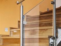 Nerezové zábradlí se skleněnou výplní nechává vyniknout dřevěnému schodišti.