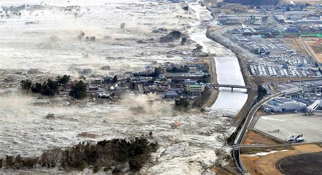 Ničivá přívalová vlna se valí na japonské pobřežní město Iwanuma. (11. března 2011)