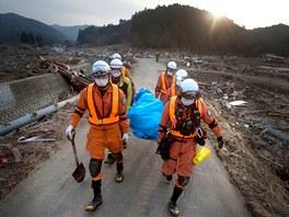 Záchranáři nesou tělo jedné z obětí v severojaponské vesnici Saito. (14. března 2011)