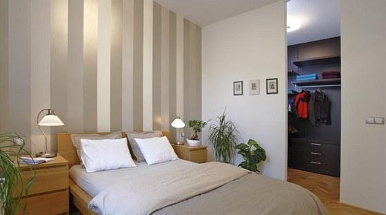 Ložnici dekorují pokojové rostliny a s nábytkem laděné textilie. Hlavní dominantou je pruhovaná tapeta Osborne & Little v čele postele.