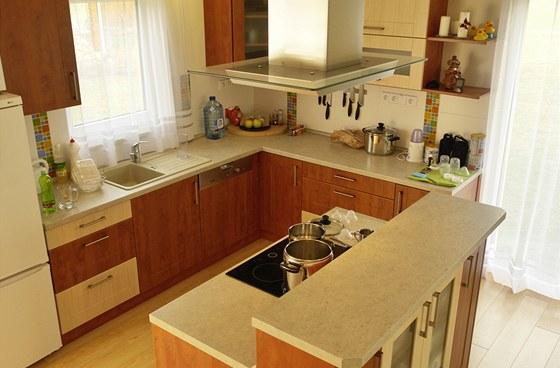 Kuchyňská linka byla vyrobena z laminovaných MDF desek. Prostor pro vaření vymezuje ostrovní varné centrum s malým barovým pultem. Zdroj: www.mujdum.cz