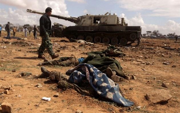Libyjští povstalci procházejí okolo těl Kaddáfího vojáků asi 35 kilometrů západně od Benghází (20. březen 2011)