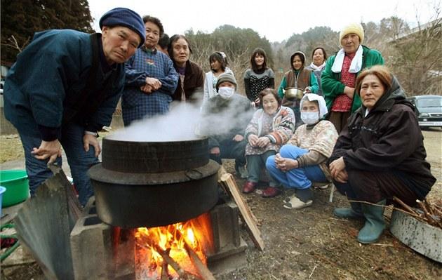 Obyvatelé m�sta Oginava, které zasáhla vlna tsunami, si va�í v kotlíku jídlo (25. b�ezna 2011)