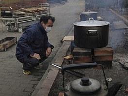 Japonec vaří jídlo nedaleko nemocnice ve městě Onagava, které zdevastovalo tsunami (25. března 2011)