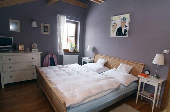 Do ložnice volili majitelé teplé klidné barvy a decentní zařízení, které je nebude při odpočinku rušit.