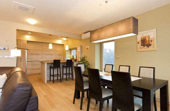 Barevný kontrast obstarává tmavě hnědý jídelní stůl a židle a světlá bambusová podlaha.