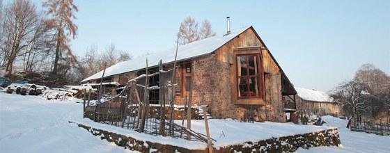 Slaměný dům zabírá prostor uvnitř rozlehlé kamenné stodoly jen zčásti.