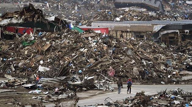 Lidé procházejí zcela zničeným městem Sendaj přesně měsíc po devastující vlně tsunami. (11. dubna 2011)