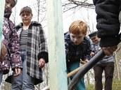 Děti sázejí jabloně ve vypálené osadě Ležáky