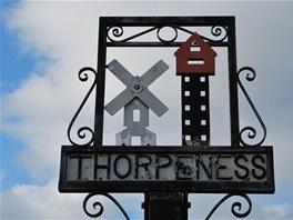 Větrný mlýn a vodárenská věž v tepaném znaku města Thorpness.