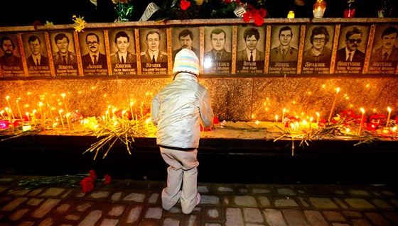 D�vka zapaluje sv��ky u pam�tn�ku ob�t� �ernobylsk� jadern� katastrofy v ukrajinsk� Slavuty�i