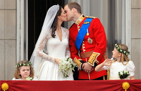 """Polibek prince Williama a jeho ženy Kate na balkoně Buckinghamského paláce. Na veřejnosti to bylo prvně, protože polibek v kostele církevní obřad zapovídá. Agentura AP polibky označila za """"krátké, sladké a plaché"""". Upozornila, že princ - vědom si historického okamžiku - se při nich začervenal. Z rozpaků ho brzy vysvobodil hluk vojenských letounů, které na počest novomanželů defilovaly nad centrem města. Polibek na balkoně sledovalo na 500 tisíc příznivců monarchie, odhaduje Scotland Yard."""