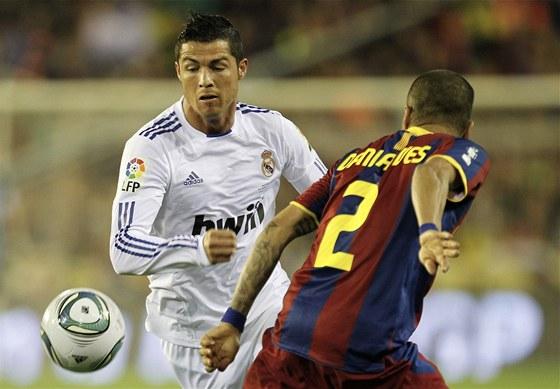 TUDY NE. Dani Alves z Barcelony (vpravo) se sna�� zastavit Cristiana Ronalda z Realu Madrid.