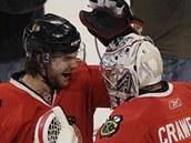 Chicagský útočník Michael Frolík (vlevo) se raduje z výhry s gólmanem Coreym Crawfordem.