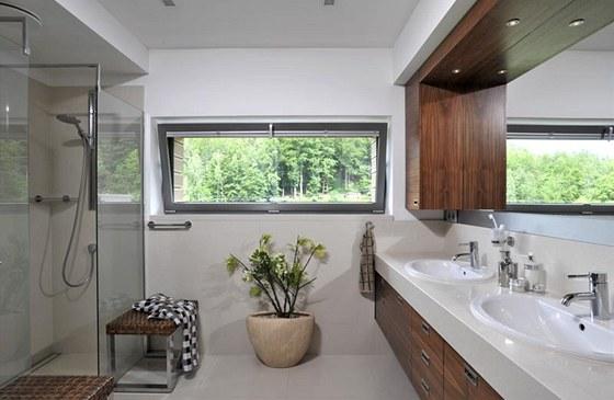 Do koupelny si manželé nepřáli vanu, ale prostorný sprchový kout. Bílá keramická umyvadla zasazená do světlé kamenné desky z quarylu barevně vyvažuje nábytek s dýhou ořechu.