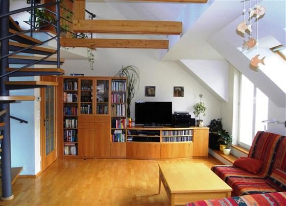 Dominantou bytu je obývací pokoj s interiérovým točitým schodištěm do podkroví.