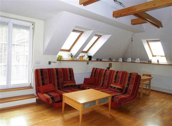 Dominantou bytu je obývací pokoj s krbem, přiznaným trámovím a otevřeným prostorem celé střechy.