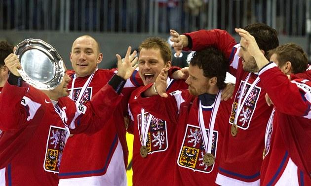JE NÁŠ! Kapitán Tomáš Rolinek s talířem pro bronzový tým na MS 2011 přijímá gratulace spoluhráčů.