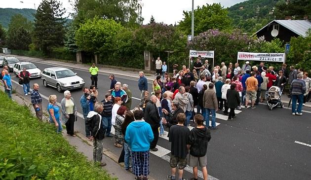 Obyvatelé ústecké �tvrti Va�ov protestovali proti oddalování dostavby dálnice D8 p�es �eské st�edoho�í. P�l hodiny p�echázeli po p�echodu a zablokovali tak dopravu.
