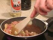 Kousky kuřecího masa a cibule na pánvi zamíchejte.