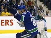 Henrik Sedin z Vancouveru se raduje z v�t�zn�ho g�lu v duelu se San Jose. G�lman Antti Niemi jen smutn� p�ihl��.