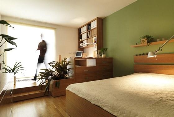Ložnice s pracovnou je v přírodních tónech.