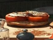 Na opečený italský chléb položte plátky rajčat, ochuťte, navrch přidejte opečenou slaninku.
