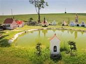 Jiří Bauer si na své zahradě po sázce s kamarády postavil zmenšený model vesnice Plešovice, nechybí v něm ani hospoda.