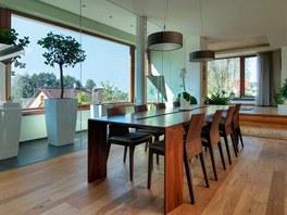 Jídelní stůl z amerického ořechu skvěle doplňují stropní závěsná svítidla značky Vibia.