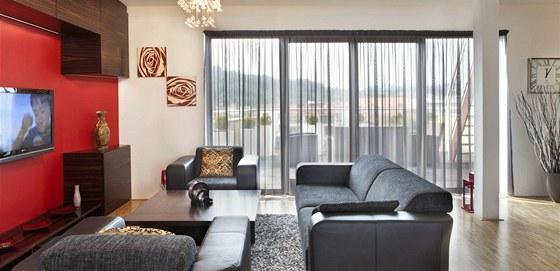 V obývací části je prosklená stěna, která při otevření propojení obývák s terasou.