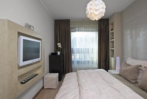 Díky světlé tapetě s jemným dekorem působí ložnice jako oáza klidu. Intimitu a dostatečné zatemnění zajišťují stylové závěsy.