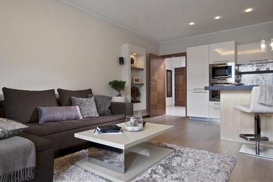 Obývací místnost je plynule propojená s kuchyňským koutem. Zajímavý prvek představuje sádrokartonová nika vedle pohovky.