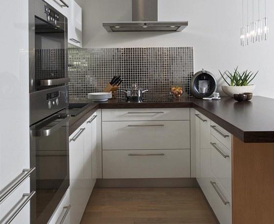 Kuchyňská linka disponuje širokým jídelním pultem, který dobře poslouží i k přípravě jídel. Opět tu hrají svou roli neutrální barvy. Pro zvýraznění zde byla použita zrcadlová mozaika.