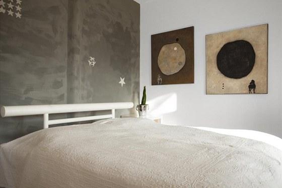 """Ložnice je pojata minimalističtěji než zbytek interiéru. Výmalba je šmouhovitě šedá, smíchaná ze dvou jasů šedé tak, aby vznikl dojem """"sídlištní"""" zdi."""