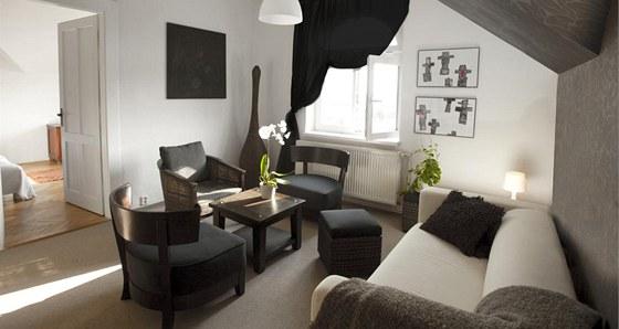 V bytě je dostatek přirozeného světla, a tak bylo možné do obývacího pokoje umístit tmavý sedací nábytek. Tmavě hnědý nábytek ve stylu moderní klasiky vytváří příjemný kontrast s bílou barvou.