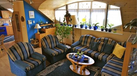 Obývací pokoj má strop obložený dřevem a dvě velká okna.