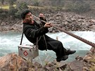 Léka� zav�ený na ocelovém lan� ru�kuje p�es �eku Nu v provincii Junnan na jihozápad� �íny