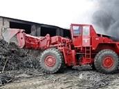 Speciální nakladač pomáhá s hašením skládky pneumatik a pryže v Boru u Skutče (7. června 2011)
