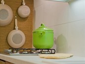 Hnědobéžovou kuchyni oživují zelené doplňky.