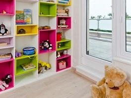 Do bílých korpusů polic jsou v dětském pokoji vloženy barevné boxy.