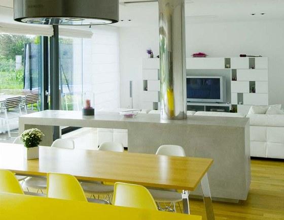 Jídelna je vybavena velkým dřevěným stolem s chromovanou podnoží a subtilními