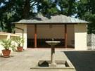 Původní garáž získala podobu stroze zařízeného pavilonu, otevřeného do atria