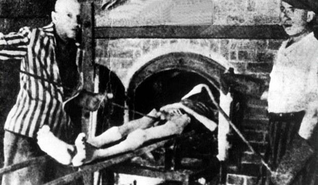 Zajatci v koncentračním táboře v Mauthausenu dávají do pece tělo mrtvého