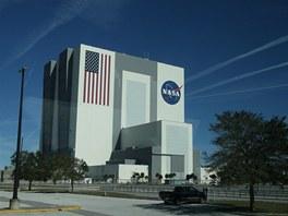 """Vehicle Assembly Building - ikonická montážní hala pojme čtyři raketoplány """"na stojáka"""". Jde o největší jednopatrovou budovu na světě, chlubí se čtyřmi největšími vraty světa a také největší vlajkou na světě. Její budoucí využítí je zatím nejisté."""