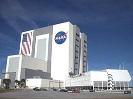 """Vehicle Assembly Building - ikonická montážní hala zkonstruovaná na pojmutí čtyř raketoplánů """"na stojáka"""". Jde o největší jednopatrovou budovu na světě, chlubí se čtyřmi největšími vraty světa a také největší vlajkou na světě. Její budoucí využítí je zatím nejisté."""