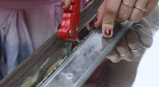 Přebytečné kusy fólie odstraňte řezákem tak milimetr od těsnění okna, abyste