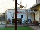 Posezení na terase za domem, pod pergolou krytou sítí, má své zrcadlově